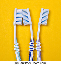three Toothbrushes on yellow background - three Toothbrushes...