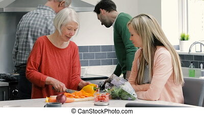 Multi-Generation Family Cooking Together - Family are...