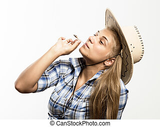 Young beautiful woman in cowboy hat and checkered shirt...