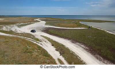 Aerial shot of a black jeep riding along the country road at the Black Sea