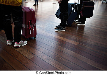 Airport, passengers awaiting boarding, legs and suitcases,...