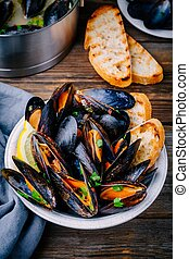Delicious seafood mussels with with sauce and parsley. Lemon...