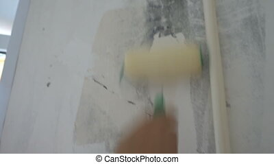 applying Wallpaper paste to the wall with a...