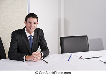 Confident businessman in boardroom waiting
