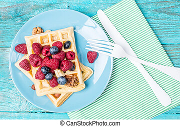 Homemade waffles with raspberries and blueberry on blue...