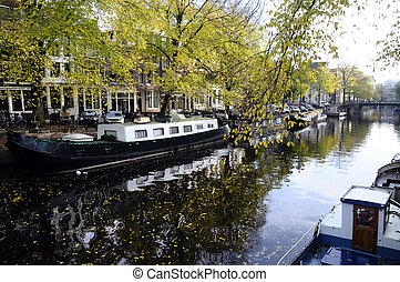 Houseboat and architecture in old city of Amsterdam in...