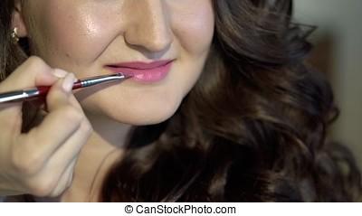 Makeup artist doing makeup with lipstick closeup