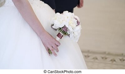 Bride and groom holding hands - Bride with bouquet and groom...