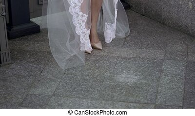 Bride in lingerie and veil walking on balcony