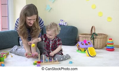 woman with her daughter play with colorful wooden blocks as...
