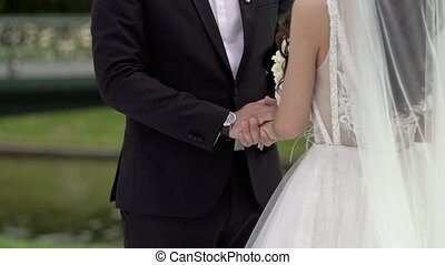 Bride and groom holding hands at wedding ceremony