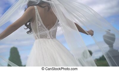 Bride walking in a park and waving veil slowmotion