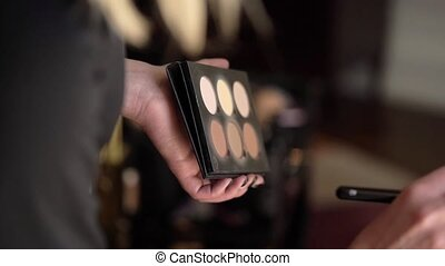 Makeup artist with cosmetics palette in hands