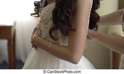 Woman helps to wear wedding dress for bride