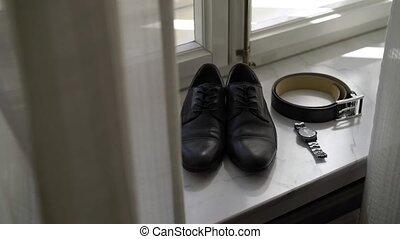 Man's accessories: shoes, belt and wrist watches near window