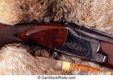 Hunting gun and a knife isolated on fur background