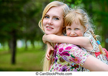 playing in piggyback - Happy mother playing with her little...
