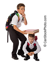 Two schoolboys playing with books together - Two smiling...