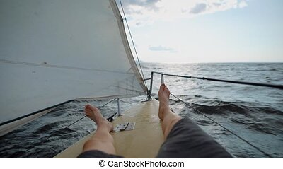 The legs of a man who are on the nose of a yacht, people go by boat along the sea waves to the distance, the sail is fluttering outside