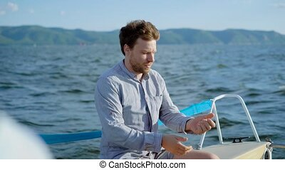 An adult man who rides a yacht adjusts his shirt, the person...