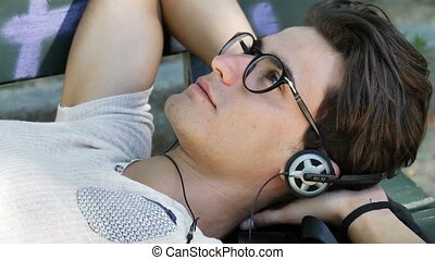 Young Man Listening to Music in Park - Close up Young Man...