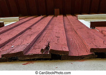 A red painted wood facade on a house which is rotten in the...