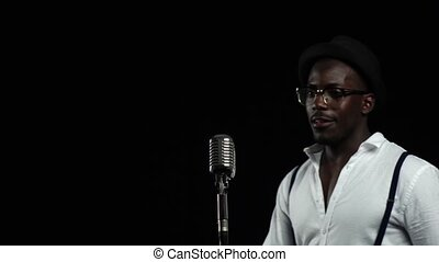 Man african american approaching the microphone singing in a...