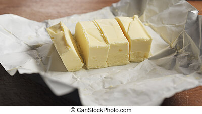 slicing butter with knife on kitchen closeup