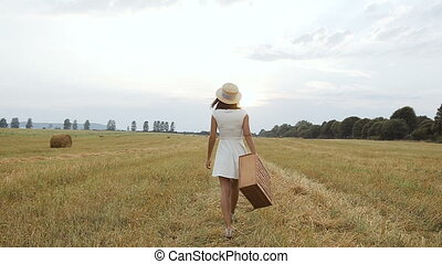 Field. Sunset. A young girl goes to a field with a straw hat...