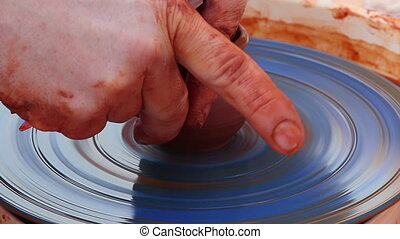 Close-up of the hand of a potter make a cup of clay.