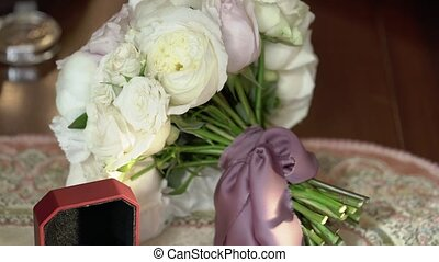 Three wedding rings in a red box and bridal bouquet shot