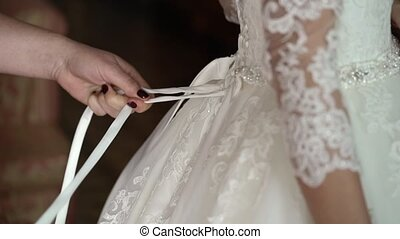 Bride dressing in wedding dress close up