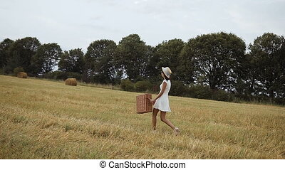 A young girl wearing a white dress with a straw hat and a...