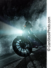 High power motorcycle chopper at night. Smoke effect on dark...