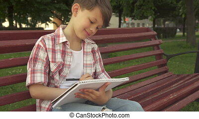 Little boy notes in exercise book on the bench