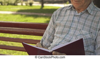 Senior man writes in his notebook on the bench