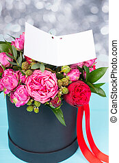 Stylish bouquet of pink and red roses with a blank gift tag...