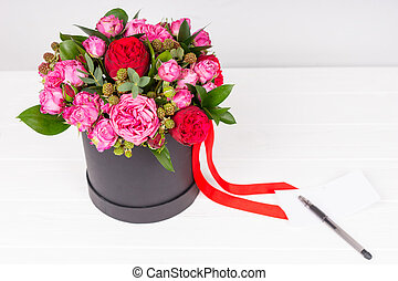 Blank gift tag with pen on it near bouquet of pink and red...