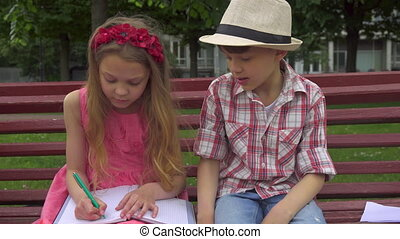 Little girl draws in the album on the bench