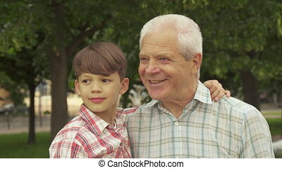 Little boy whispers in his grandpa's ear