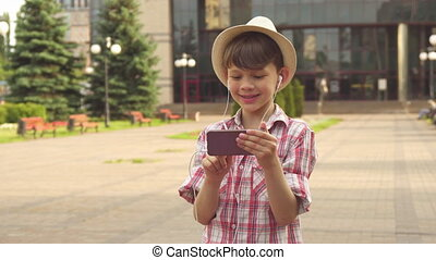 Little boy listens to music on his smartphone