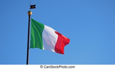 Waving big Italian flag against blue cloudless sky - Waving...