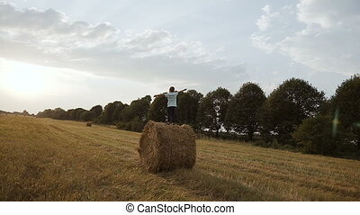 In a field on a haystack there is a boy and looks at the...