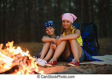 Tired and happy kids sitting at campfire.