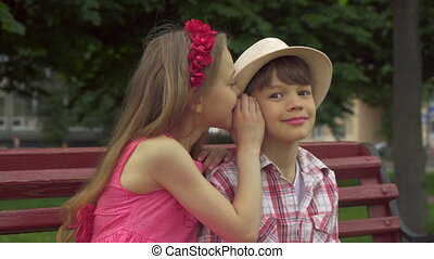 Little girl shares secrets with boy on the bench