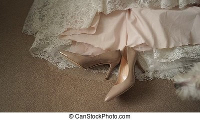 Shoes lie on the background of the bride's dress.