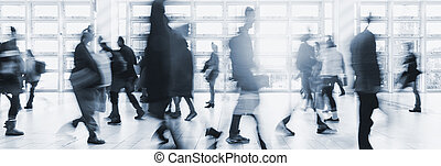 blurred crowd commuting traveling walking in a modern hall -...