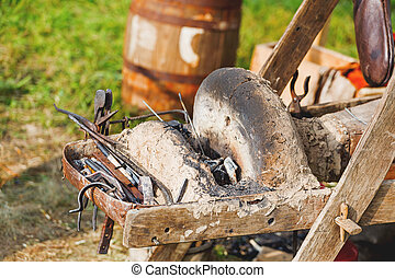 Iron old fashioned tools on portable forge. Old furnace and...