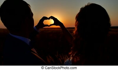 couple wedding hands forming a heart shape with sunset...