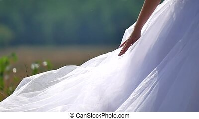 the bride on nature touches the dress with her hand. nature...